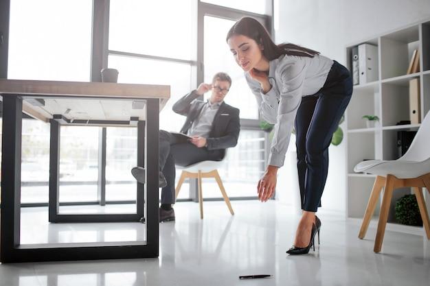 섹시 한 젊은 여자는 바닥에서 펜을 아래로 구부립니다.
