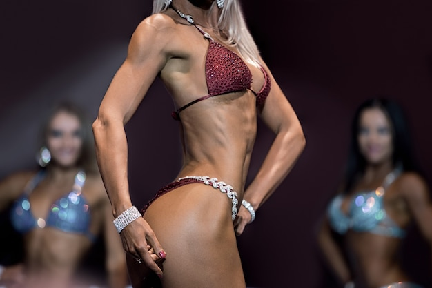 Sexy young woman in bikini. fitness bikini athlete on stage. sport gives way to success. perfect proportions of female body.