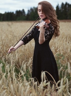 Sexy young woman in a black dress enthusiastically playing the violin in a wheat field in a strong wind