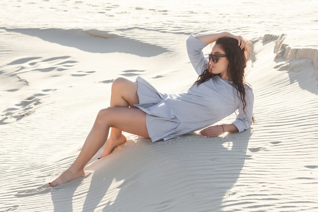 Sexy young woman in the desert. pretty girl on the sand