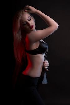 Сексуальная молодая женщина в черном нижнем белье раздевается в студии