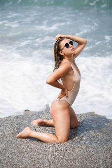 閉じた水着のセクシーな若い女性は、海沿いの砂浜に立っています。海で休暇中のヨーロッパの外観の女の子