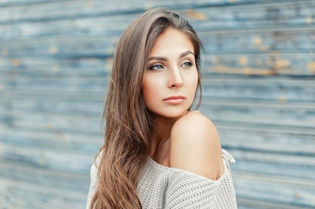木製の壁の近くに灰色のセーターと裸の肩のセクシーな若い女性
