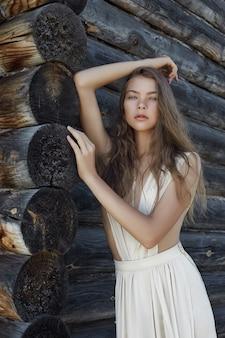 Сексуальная молодая женщина в легком белом платье позирует в деревне возле старого дома
