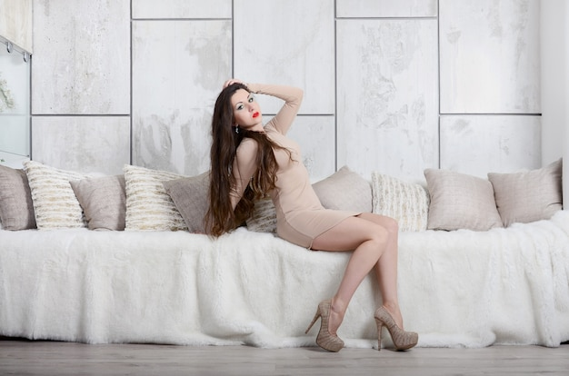 Сексуальная молодая женщина в элегантном бежевом платье и на высоких каблуках рядом со сливочной кроватью со множеством подушек в гостиничном номере