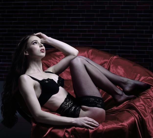 그의 다리와 가죽의 자에 앉아 란제리에 섹시 한 젊은 여자