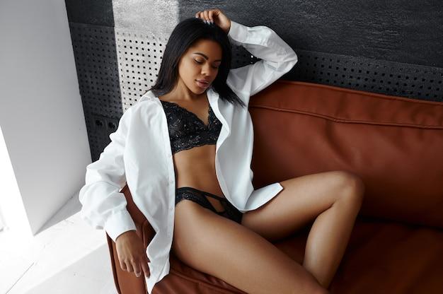 럭셔리 란제리에 섹시 한 젊은 여자는 소파에서 휴식