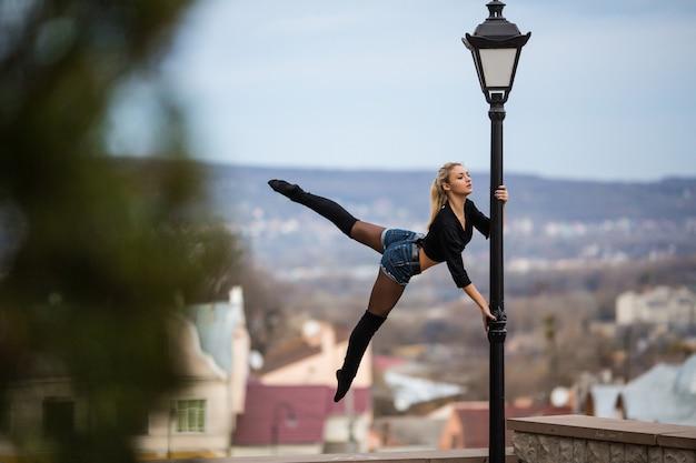 Сексуальная молодая женщина в бассейне танцует стиль танца на открытом воздухе на улице