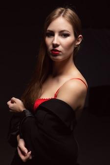 Сексуальная молодая женщина в красном нижнем белье и мужская куртка в темной комнате