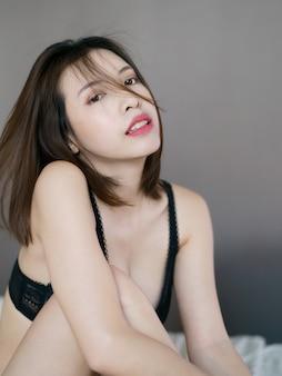 관능적 인 검은 란제리에 섹시 한 젊은 여자는 침대에 포즈.