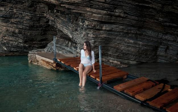 海の洞窟に座っている白いシャツを着たセクシーな若い女性