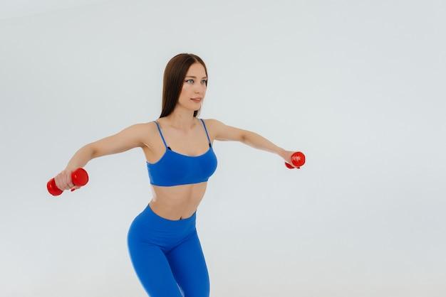 セクシーな若い女性が青いトラックスーツで縄跳び。フィットネス、健康的なライフスタイル。