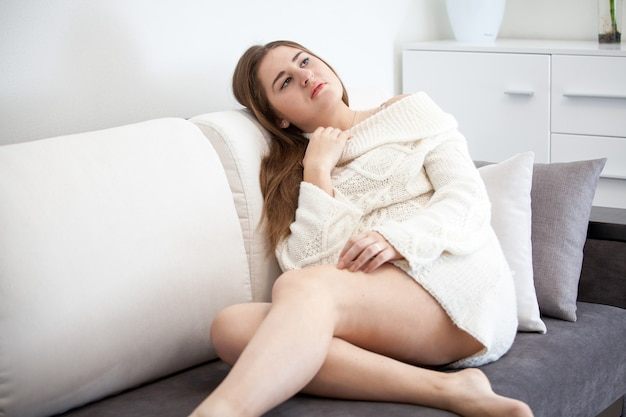 Sexy young woman lying on sofa in modern house