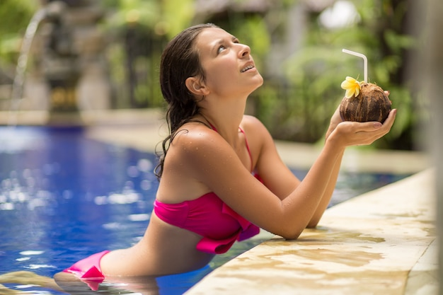 Sexy young woman in pink swimsuit having coconut drink in swimming pool on vacation.