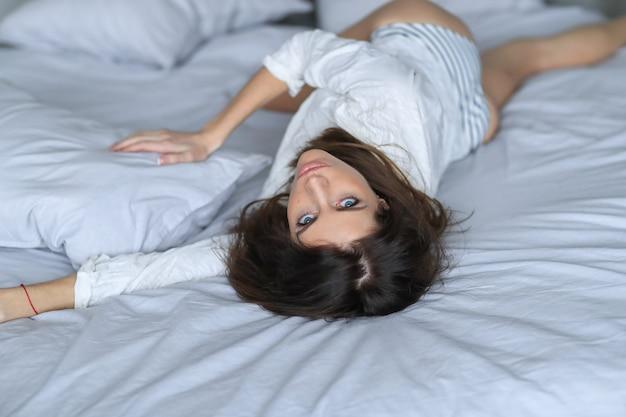 ベッドでポーズをとるセクシーな若い女性