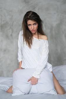 섹시 한 젊은여자가 침대에서 포즈