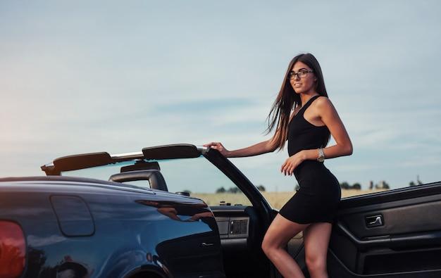 차에서 포즈 섹시 한 젊은 여자
