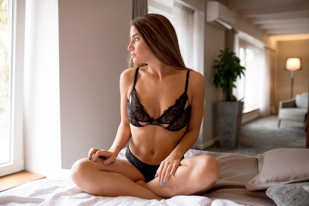 Sexy young woman sitting on bed