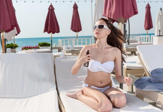 リゾートの晴れた気候で、ラウンジチェアに座って日焼け止めローションを体にスプレーするセクシーな若い女性。