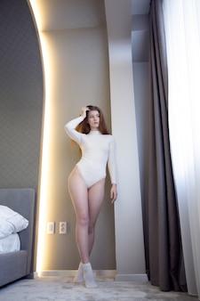 セクシーな若い女性が彼女の下着の窓に立っています