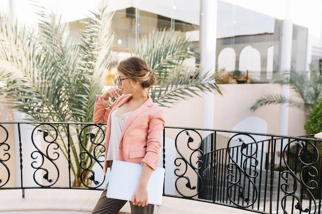 セクシーな若い女性、美しいバルコニー、ホテルのテラス、庭に手のひらでレストランに立っている銀のラップトップを持つ学生。おしゃれなメガネ、ピンクのジャケット、ベージュのブラウス、キュートなヘアスタイル。