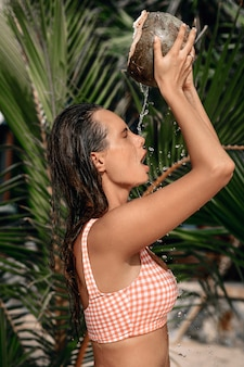 Sexy and young woman in a stylish bikini swimsuit holding a coconut on the tropical shore.