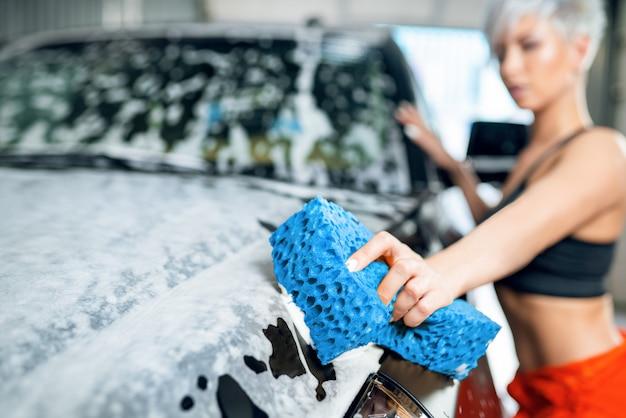 Сексуальная молодая женщина моет машину в автомойке