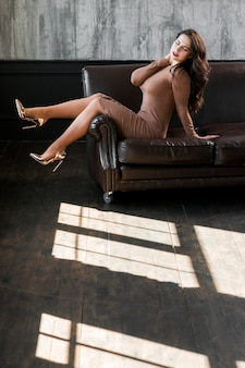 Sexy young woman wearing golden high heels sitting on sofa
