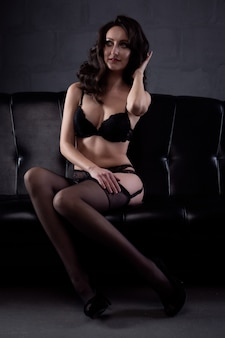 革のソファの上にレースの黒い下着で美しいボディを持つセクシーな若い女性
