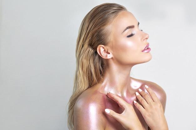 完璧な肌と彼女の首と肩に金属の輝きを持つセクシーな若い女性。テキスト用のスペース Premium写真