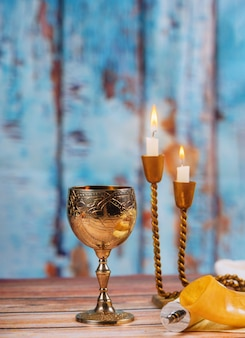 Shabbat challah bread wine and candles on wooden table