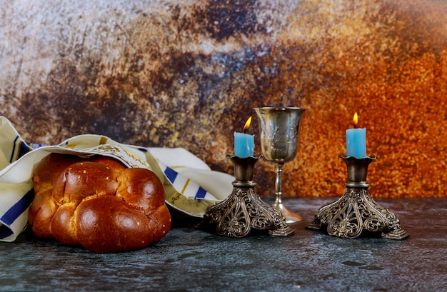 Shabbat eve with challah bread, sabbath candles and kiddush wine cup.