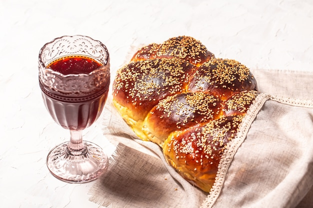 Shabbat or sabbath kiddush ceremony. challah bread, glass of red kosher wine