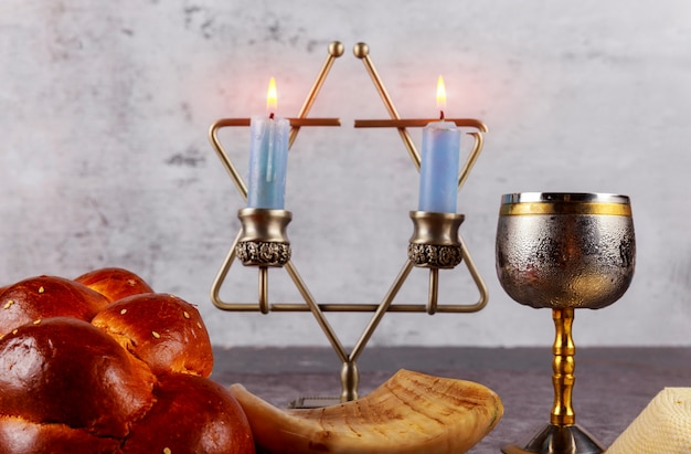 Shabbat with challah bread on a wooden table candles and cup of wine.