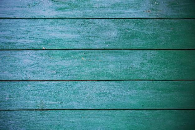초라하고 아주 오래된 녹색 파란색 나무 울타리.