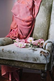 Потертое кресло с цветущими цветами на сиденье
