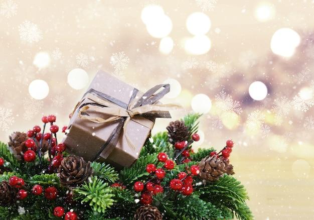 Потертый шикарный рождественский подарок в венке с ягодами и сосновыми шишками