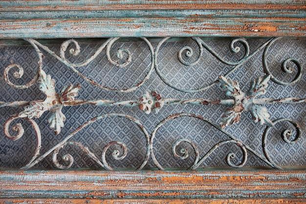 Потрепанная дверь из темного окрашенного дерева в обрамлении двери со старинными декоративными металлическими решетками. узорчатые текстуры решетки. архитектурные детали старинной двери
