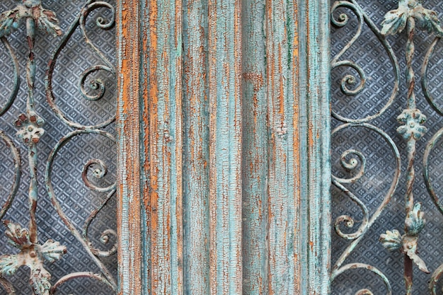 Shabby dark  painted wooden framed door with antique ornate metal gratings  patterned lattice textures. architectural details of vintage door of old building