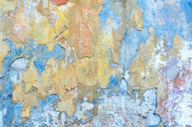 Shabby grunge texture of a stucco coated plaster wall with many layers of paint