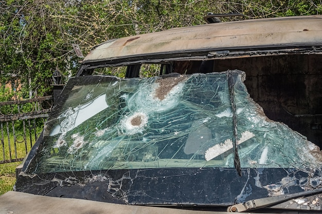 Shabby weathered car with broken bulletproof glass after shooting.