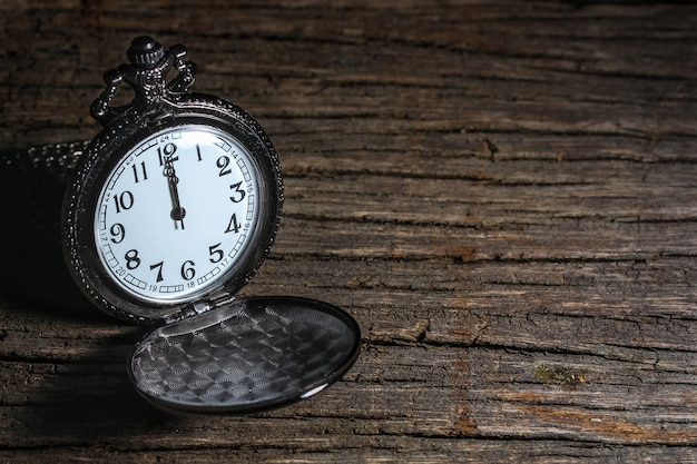 Shade of light and dark of luxury vintage black pocket watch on wooden table, abstract for time concept with copy space