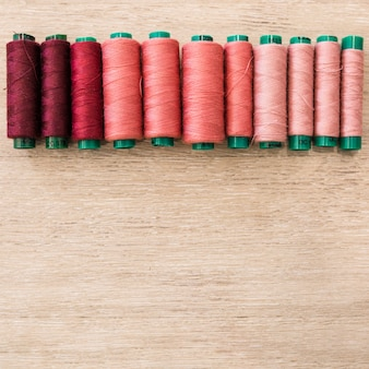 Shade of red spools on wooden background