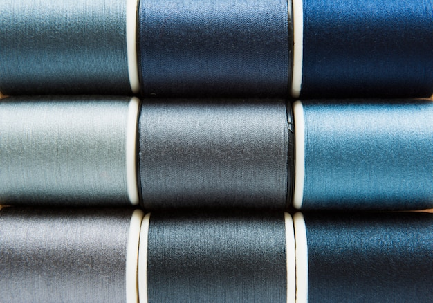 Shades of gray and blue sewing threads background closeup