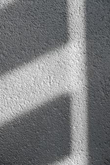 タイル張りの壁のブラインド窓からの影と光朝の光と壁の影