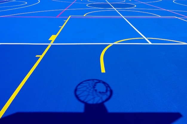 Shadow of a basketball basket on the floor of the court