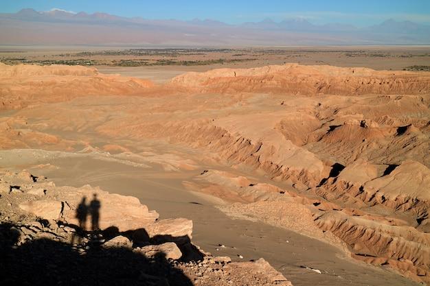 Shadow of a couple exploring the moon valley or valle de la luna, atacama desert, san pedro atacama, chile