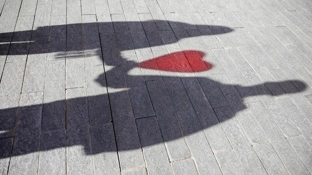 Shadow of couple with balloon in form of heart