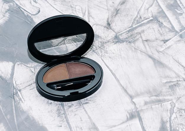 眉毛の影、茶色のアイシャドウ、コンクリートの背景に眉ブラシ、
