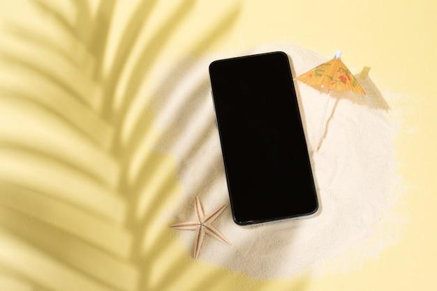 Тень от пальмового листа на желтом фоне, смартфон на песке с зонтиком и морской звездой, летняя концепция, макет, крупным планом.